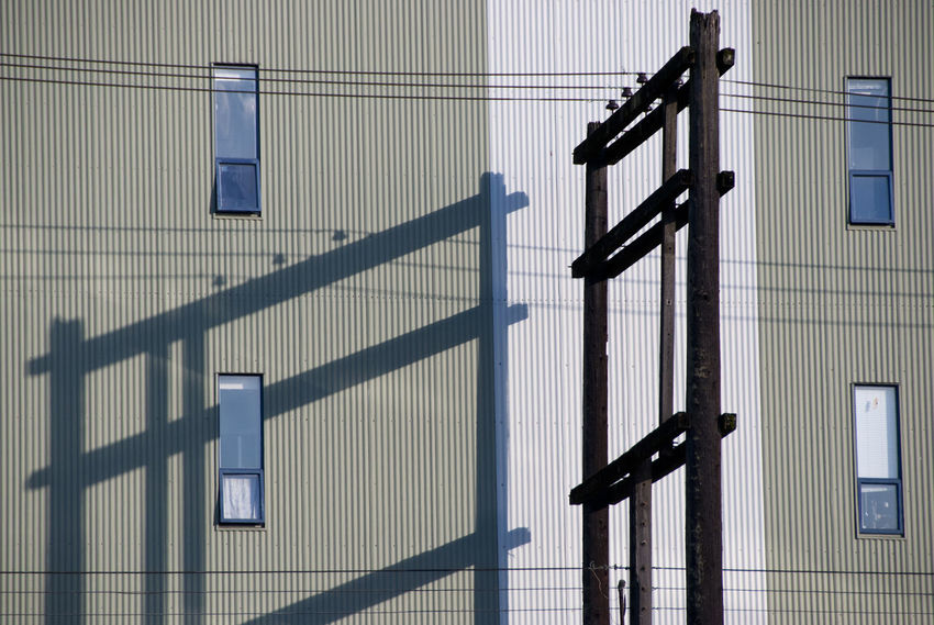 A power pole casts a shadow on an industrial building. Aluminum Architecture Building Business Finance And Industry Commercial Day Grey Indulgence Metal Modern No People Outdoors Pole Power Property Shadow Storage Structure Sunset Textured  Twilight Urban Wall - Building Feature Warehouse Window