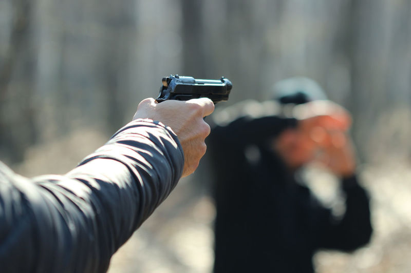 Cropped Hand Of Man Aiming With Gun At Person