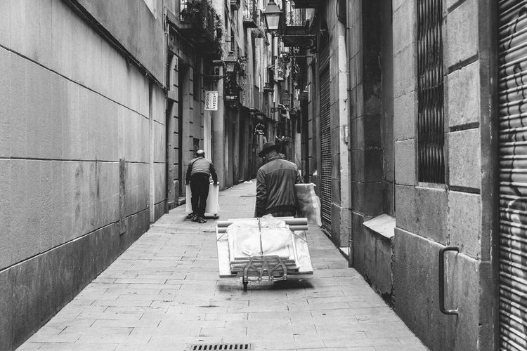 Delivery and the Artist Adult Architecture Art Artist Bercelona Black & White Black And White Blackandwhite Building Exterior Carrying City Day Delivery Exposition Hat Lifestyles Men Narrow Street Outdoors People Real People Rear View Trolley Two People
