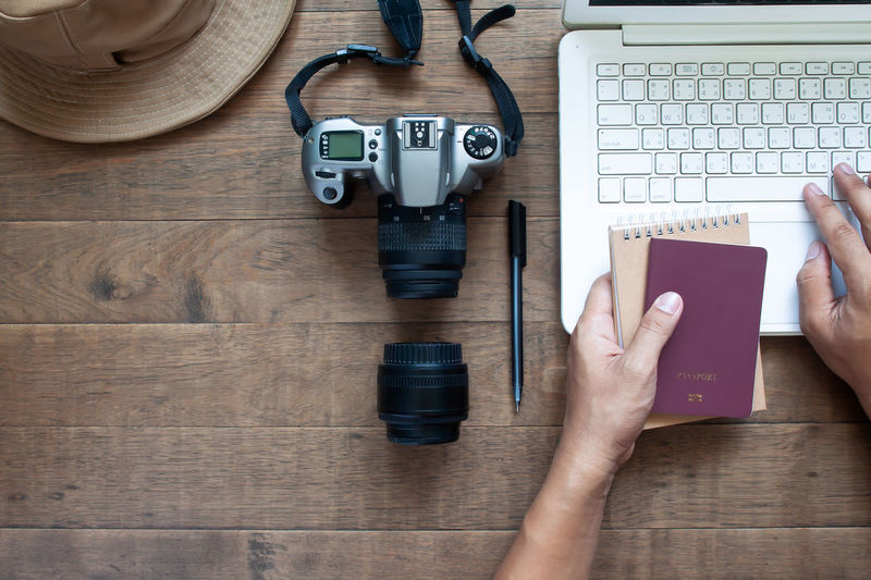 Overhead view of man hands using laptop and holding passport and camera on wooden background, travel, top view, flat lay, work, internet, online, technology, computer, business, creative, office, office work, camera, hat, holiday, summer, weekend, lifestyle, tourist, pen, plan, passport, copy space, copyspace, laptop, working, desk, keyboard, data, workspace Travel Tourist Holiday Summer Keyboard Finger Computer Equipment Holding Wood - Material High Angle View Indoors  Directly Above Photography Themes Human Body Part Computer Portable Information Device Communication Wireless Technology One Person Connection Table Real People Hand Technology Human Hand Photographer Camera Wooden Small Office Camera - Photographic Equipment