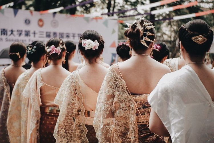 Rear view of women in traditional clothing standing outdoors