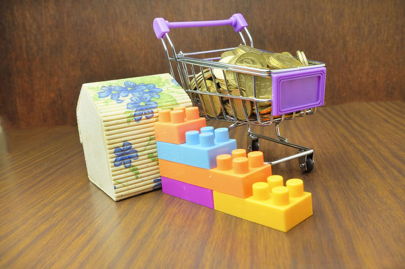 Close-up of coins in shopping cart with house model and toy blocks on wooden table
