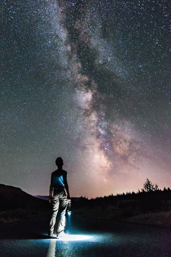 Rear view of young man looking at star field at night