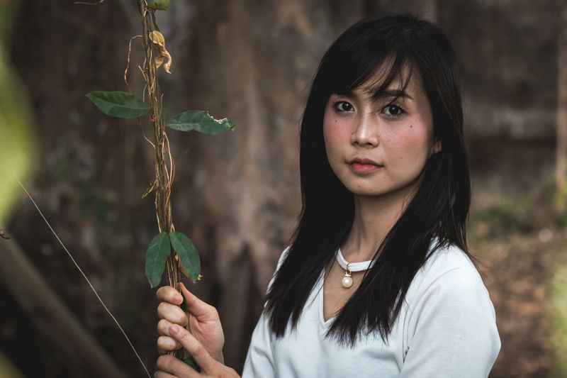 Portrait Of Young Woman Holding Plant In Forest