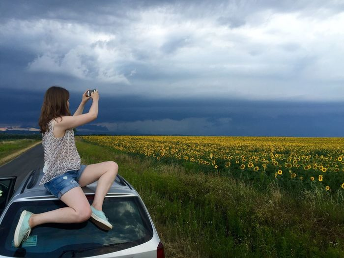 Woman sitting on car roof while photographing sunflower field against cloudy sky