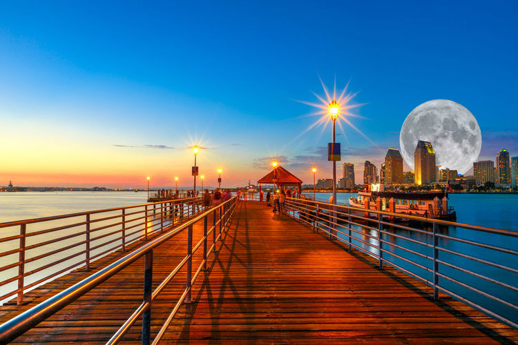 Scenic twiligtht view of Coronado wooden pier with docked ferry boat on Coronado Island, California, USA. San Diego skyline and urban downtown cityscape with big full moon over San Diego Bay. Coronado Coronado Beach Coronado Island Sea Beach San Diego California United States America American Skyline Seascape Cityscape Sun Dock Port Holiday Vacations Sunset Night Moon Moonlight Pier Sky Architecture Water Built Structure Railing Illuminated Nature Building Exterior Street Light Bridge The Way Forward Connection Travel Destinations No People Direction Scenics - Nature Bridge - Man Made Structure Outdoors