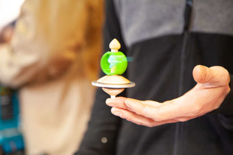 Midsection of man holding spinning top on finger