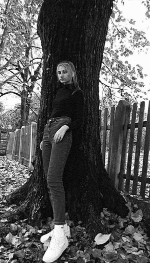 Portrait of woman standing by tree trunk
