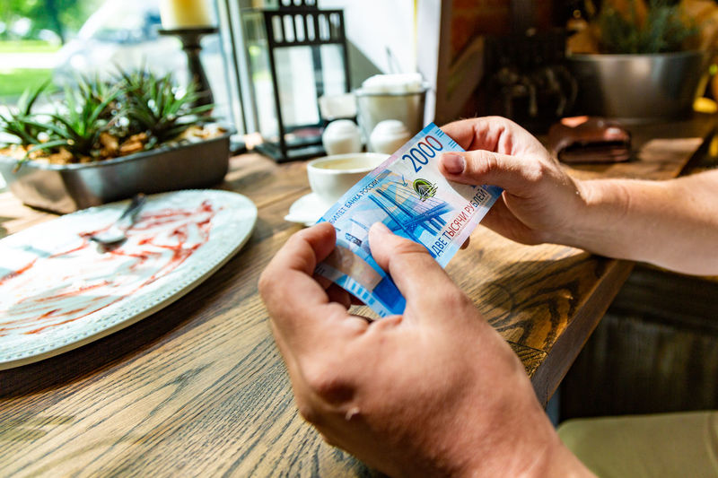 Close-up of hands holding banknote at restaurant