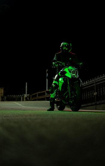 Man sitting on field at night