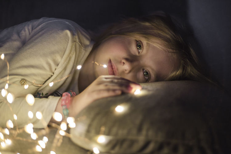 One Person Indoors  Portrait Lying Down Illuminated Lifestyles Real People Child Headshot Glowing Lighting Equipment Childhood Girls Selective Focus Leisure Activity Front View Casual Clothing Home Interior Contemplation Innocence Tea Light