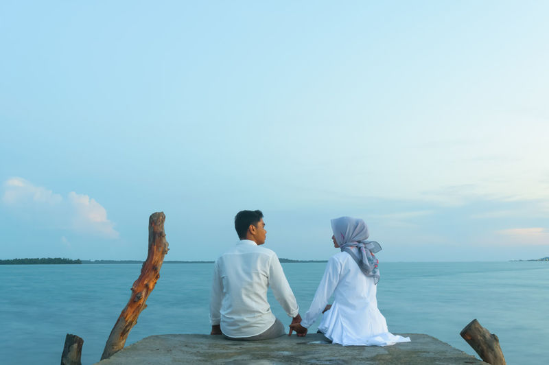 Relationship Couple Romantic Romance Blue Sky Calm Sea Waterfront Sitting Couple - Relationship Prewedding Concept Long Exposure Slow Shutter Sunset Lifestyles Wedding Sunlight Water Sea Beach Full Length Togetherness Relaxation Blue Rear View Jetty Wedding Dress Bridegroom Wedding
