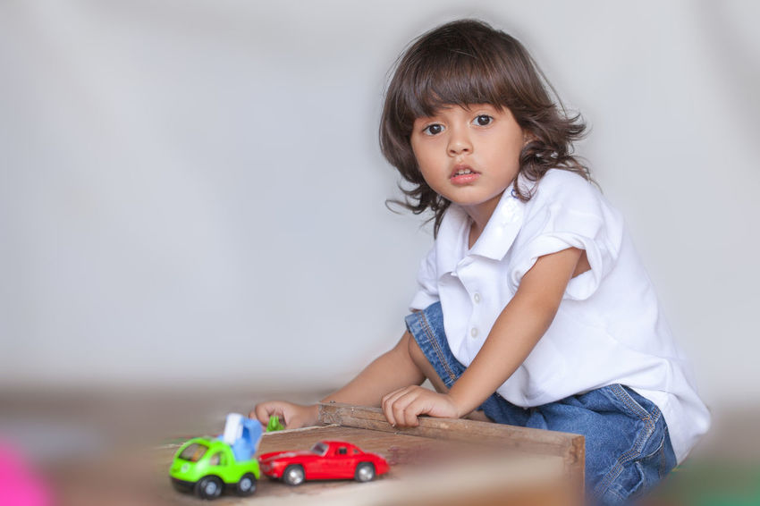 a long hair boy in white shirt and jean playing toy on the ground while waiting for his mom in Mother Day Long Hair, Don't Care. People, Smile, Bangs Boy,  Brown Hair Casual Clothing Child Childhood Females Front View Garland, Girls Hair Hairstyle Indoors  Innocence Looking At Camera Offspring One Person Play, Kids, Family, Fun, Smile Portrait Sitting Toy Toy, Women