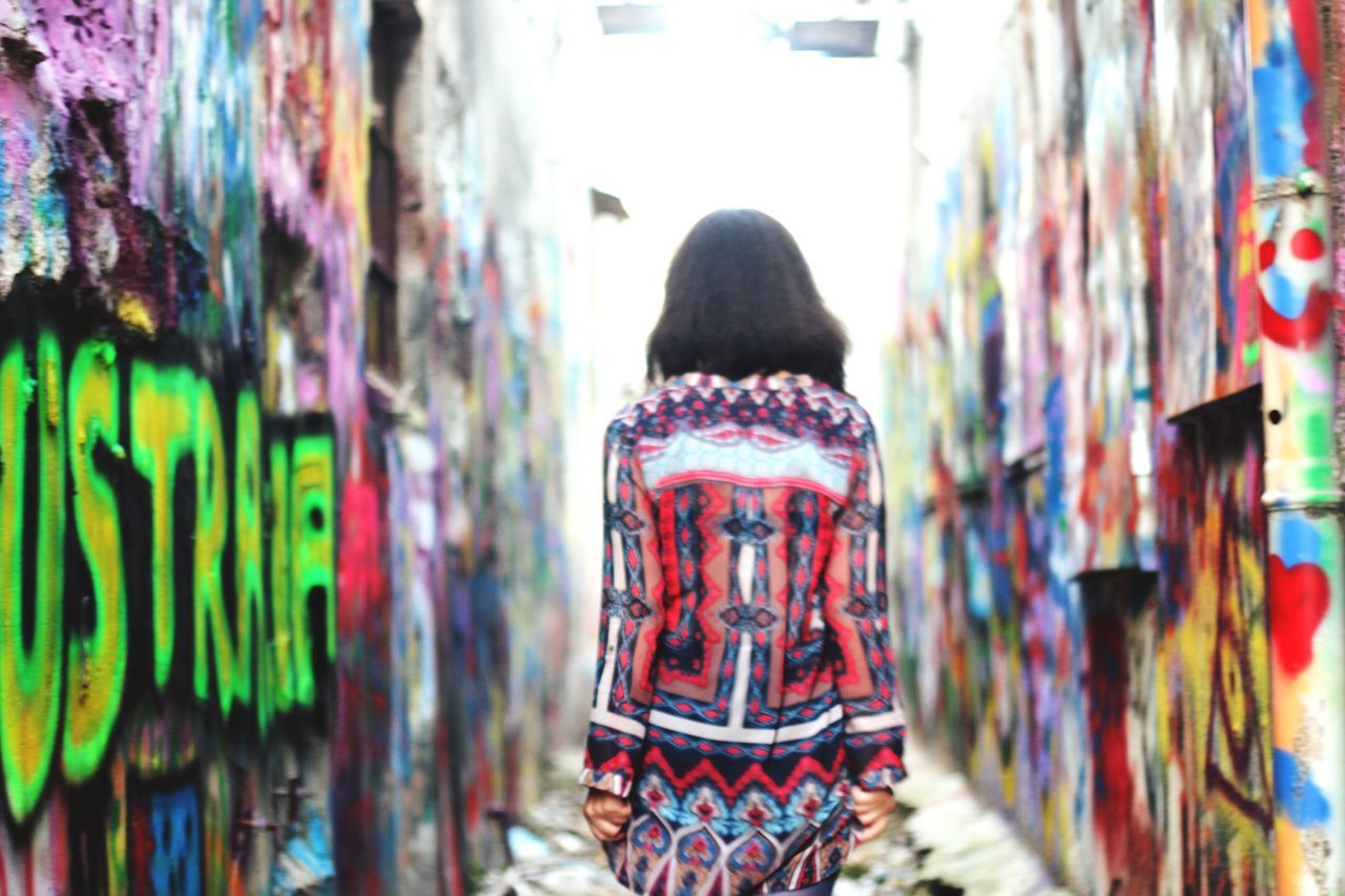 Rear view of woman walking amidst graffiti