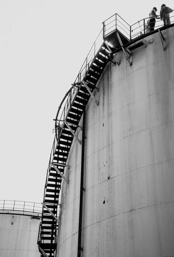 Oil depot workers work on tanks Staircase Railing Steps And Staircases Low Angle View Steps Built Structure Architecture Stairs Spiral Day Clear Sky No People Outdoors Factory Hand Rail Building Exterior Spiral Staircase Sky