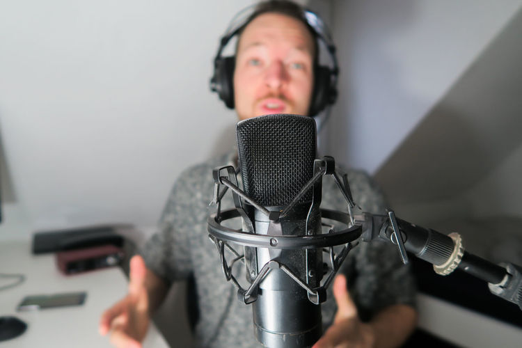 Young male podcaster, youtuber with condenser microphone Input Device Microphone Music One Person Indoors  Headphones Technology Adult Listening Front View Portrait Studio Arts Culture And Entertainment Communication Recording Studio Mid Adult Headshot Audio Equipment Occupation Sound Recording Equipment