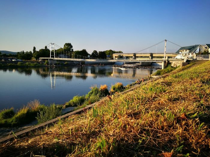 Bridge over mures river against blue sky