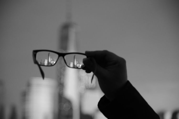 Cropped hand holding eyeglasses against buildings