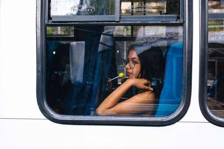 Woman sitting by window at railroad station