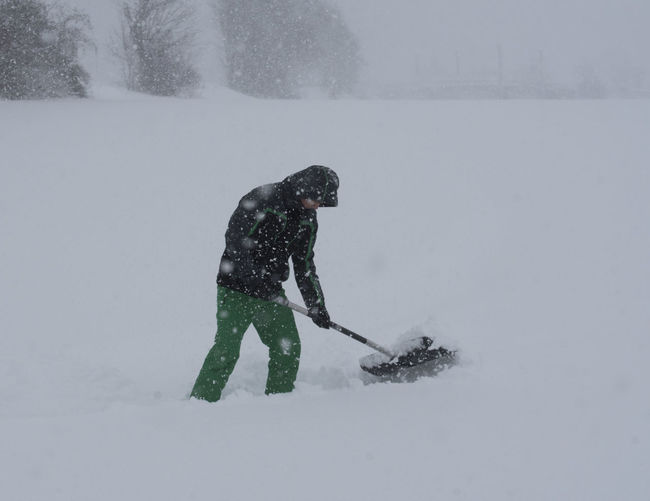 Full length of man on snowcapped field during winter