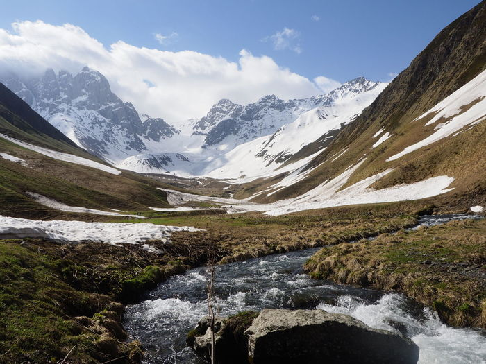 Scenic view of stream amidst snowcapped mountains against sky