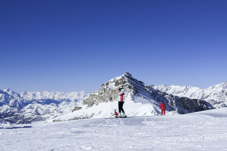 Low angle view of people skiing on snowy landscape against clear blue sky