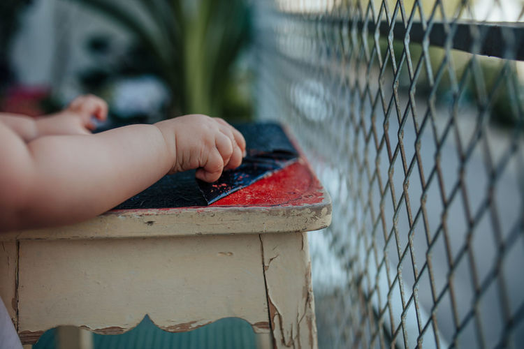 Cropped hands of baby removing plastic from stool by fence