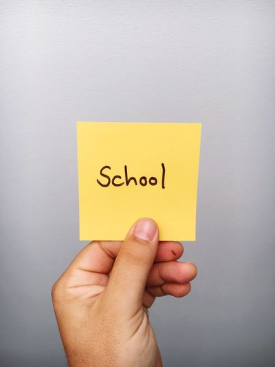 Cropped Hand Of Person Holding School Text On Adhesive Note Against Gray Background