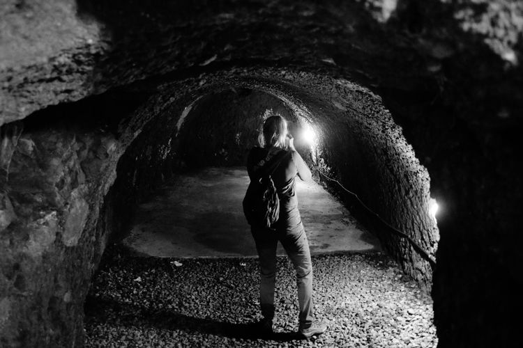 Rear view of woman standing in tunnel at night