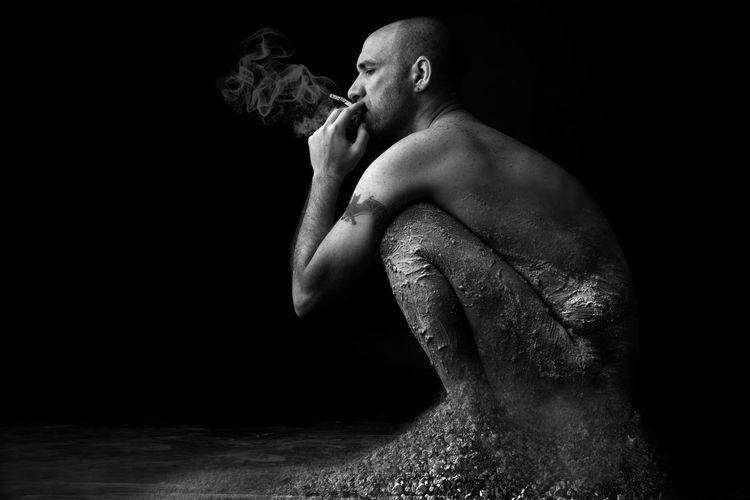 Side View Of Man With Dirt Smoking Cigarette Against Black Background