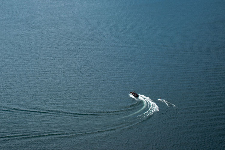 High angle view of a boat and wake boarder