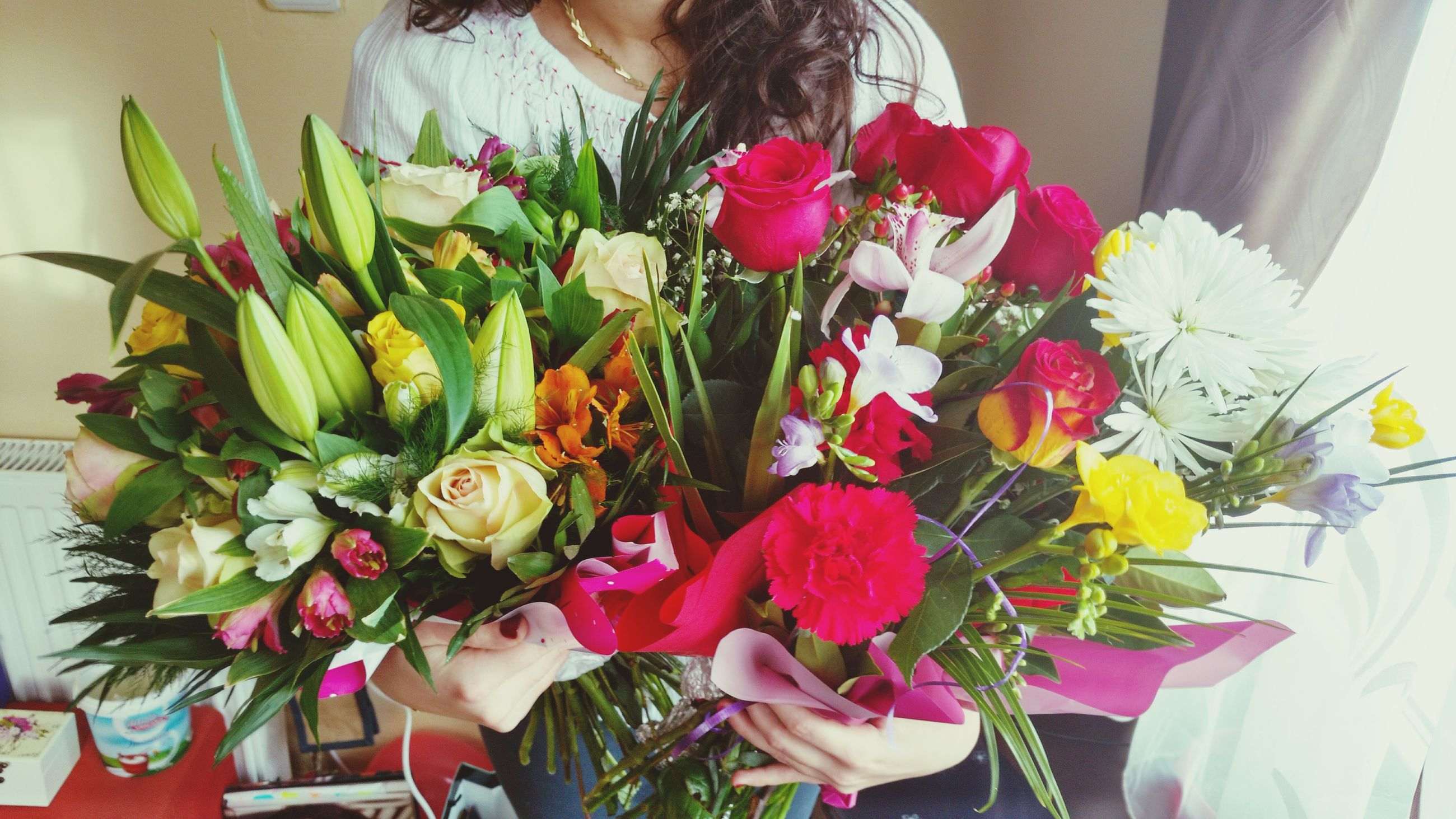 flower, indoors, freshness, bouquet, vase, fragility, lifestyles, bunch of flowers, variation, holding, home interior, flower arrangement, table, standing, person, petal, casual clothing, leisure activity
