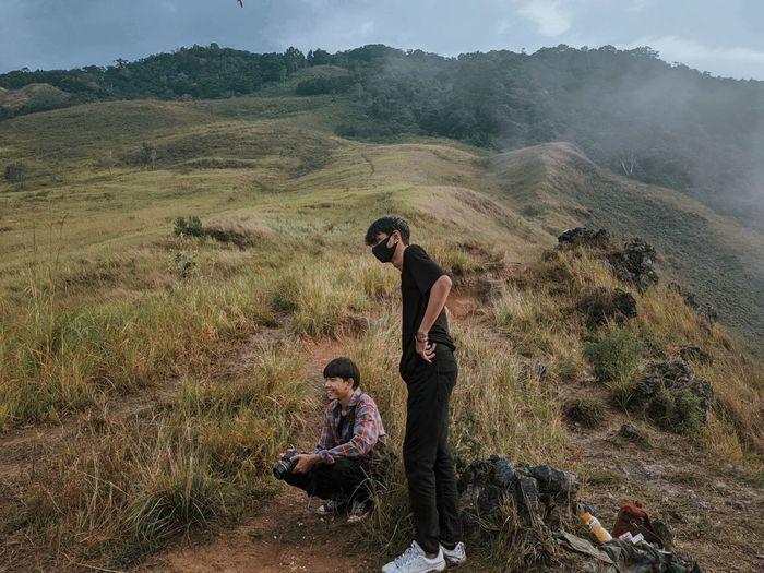 Young men on landscape against sky