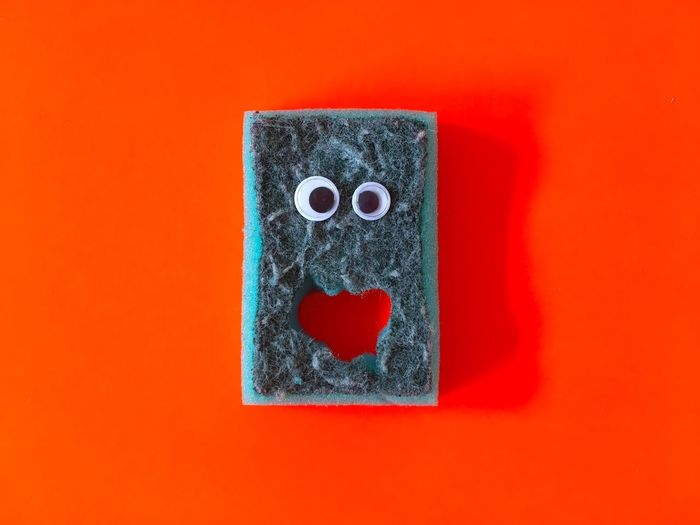 Directly Above Shot Of Sponge With Anthropomorphic Face On Red Background