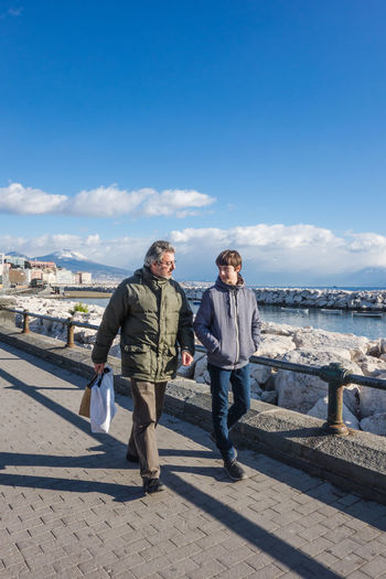 Father and son talking while walking on promenade against blue sky