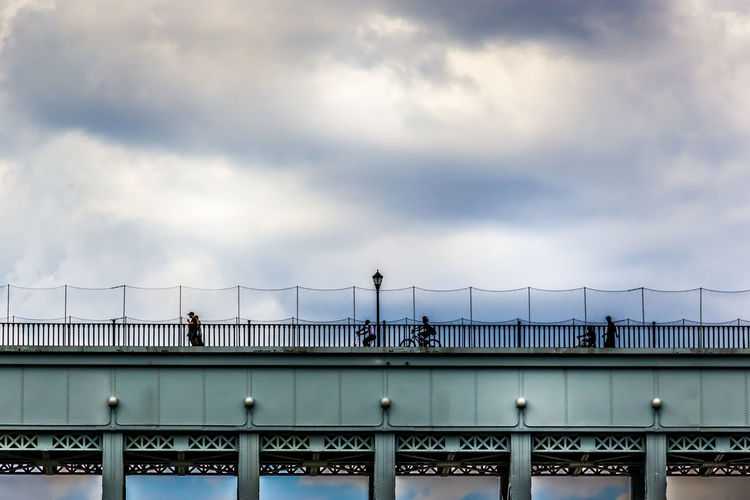 People walking on bridge against sky