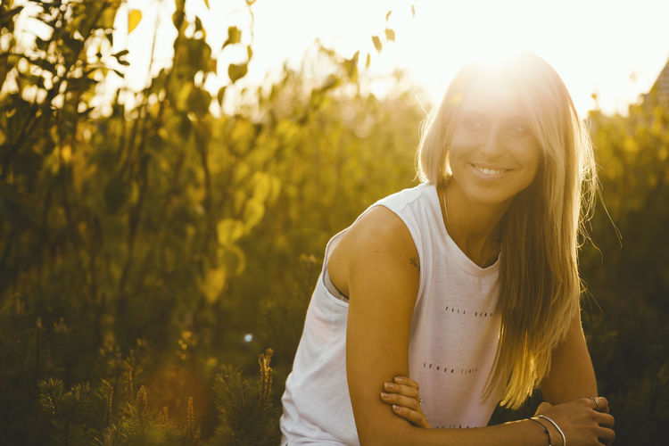 Smiling young woman on field during sunny day