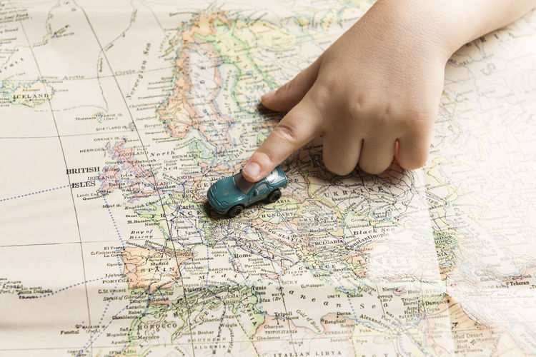 Cropped hand of child holding toy car on map