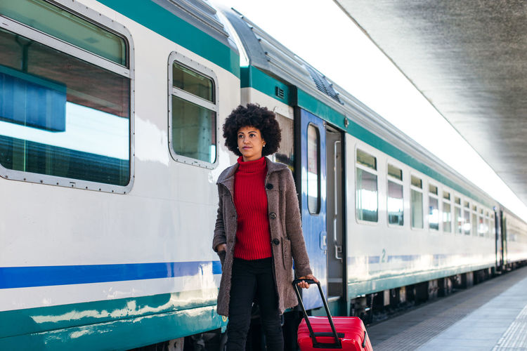 Portrait of woman standing on train at railroad station