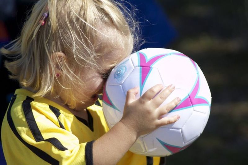 Close-up of girl holding soccer ball while crying outdoors