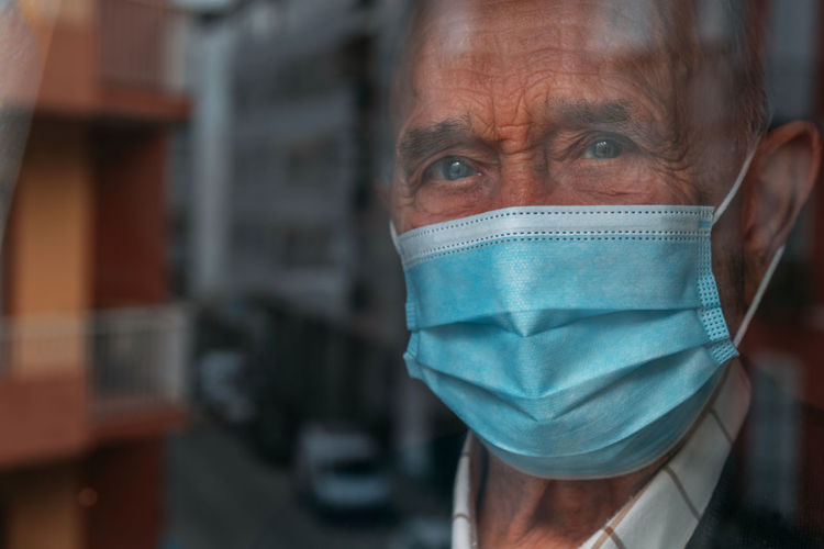 Portrait of man wearing mask looking through window