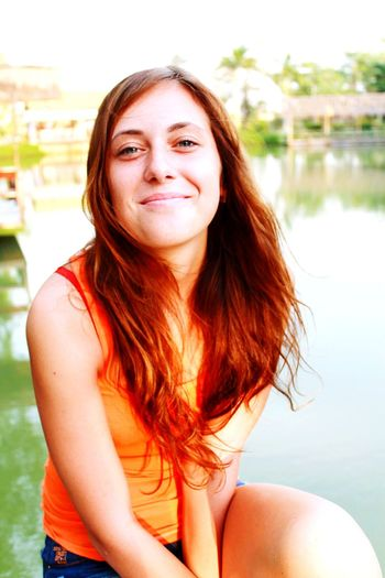 Portrait of smiling woman sitting against lake