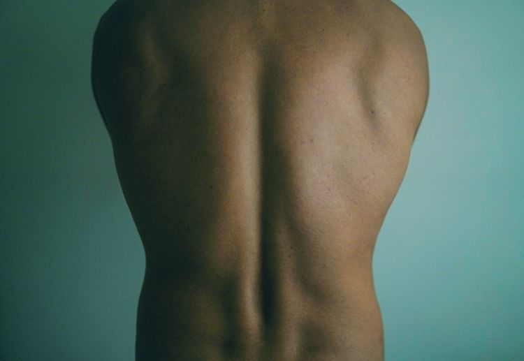 Rear view of shirtless man standing against blue background