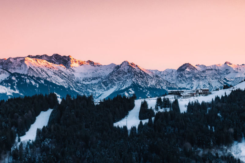 Snow covered mountains against sky during sunset