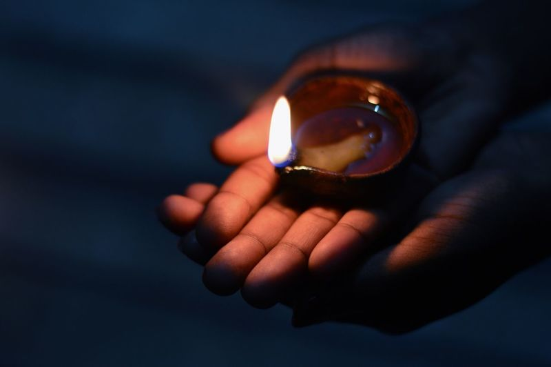 Close-Up Of Cropped Hand Holding Lit Diya At Night