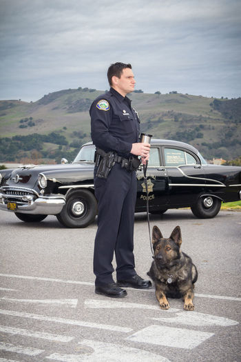Adult Cloudy Day Dog Full Length Horizon K9 Law Enforcement Law Enforcement Officer One Animal One Person Police Police Canine Police Car Police Officer Scenic Side View Uniform