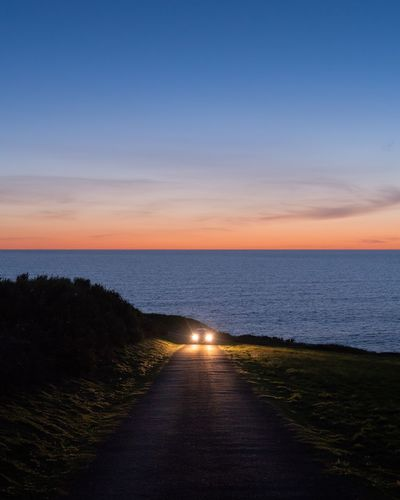 Lights Car Sky Water Sea Scenics - Nature Sunset Beauty In Nature Tranquility Tranquil Scene Nature Horizon Horizon Over Water Land Road Outdoors Dusk The Great Outdoors - 2018 EyeEm Awards The Traveler - 2018 EyeEm Awards