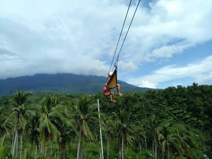 People On Zip Line Against Mountain