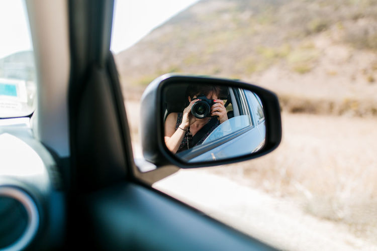 Reflection of woman photographing through side-view mirror of car