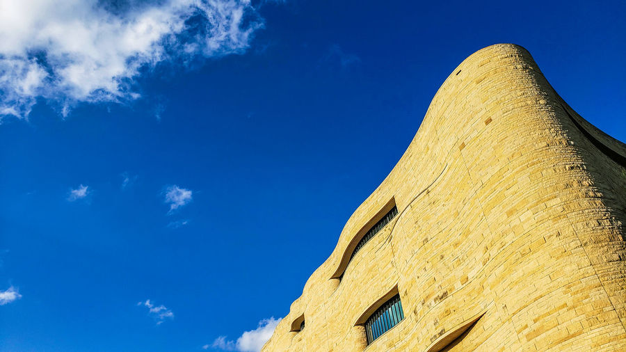 National Museum of the American Indian in Washington, DC. Native American Indian Curved  Curves Curves And Lines Organic Building Building Exterior Low Angle View Sky Architecture Architecture_collection Ancient History Blue Triangle Shape Archaeology The Past Sky Geometric Shape Stone Material Desert Arid Climate Square Shape Tall Urban Scene Exterior The Architect - 2019 EyeEm Awards